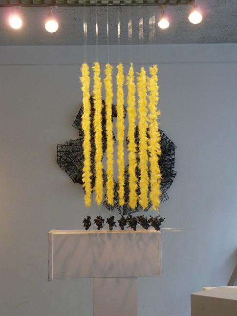 MIROIR AUX ALOUETTES : Suspension de 100 fils nylon de 1M chacun sur lesquels sont collées des plumes jaunes. chaque fil est terminé par une boule de plâtre , au-dessus d'un miroir. Au mur assemblage structures en plastique, entourées de laine noire.